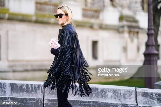 Charlotte Groeneveld wears sunglasses a black leather fringed jacket sneakers shoes outside Elie Saab during Paris Fashion Week Womenswear...