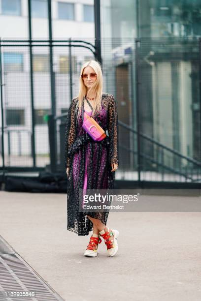 Charlotte Groeneveld wears sunglasses, a black mesh lace long jacket, a pink dress, shoes with red shoelace, a bicolor purple and orange shoulder...