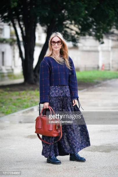 Charlotte Groeneveld wears sunglasses, a blue checked pullover, a blue floral print skirt, a burgundy leather Chloe bag, leather boots, outside...