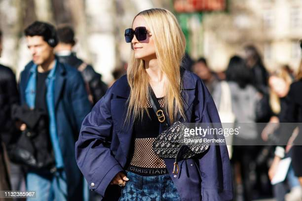 Charlotte Groeneveld wears sunglasses a Dior monogram Saddle bag a blue jacket a black fishnet mesh top blue printed cropped pants fishnet leggings...