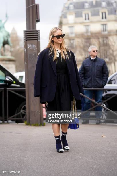 Charlotte Groeneveld wears sunglasses, a navy blue oversized blazer jacket, a black dress, a blue bag, socks, pointy shoes, outside Miu Miu, during...