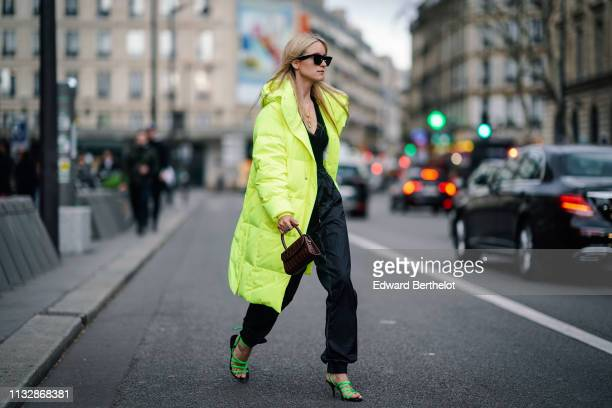 Charlotte Groeneveld wears sunglasses a neon yellow long puffer coat a brown leather bag sunglasses outside Redemption during Paris Fashion Week...