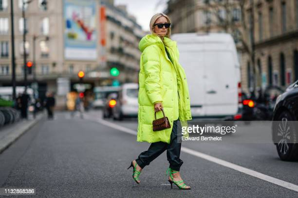 Charlotte Groeneveld wears sunglasses, a neon yellow long puffer coat, a brown leather bag, sunglasses, outside Redemption, during Paris Fashion Week...