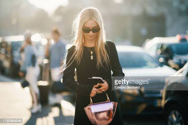 Charlotte Groeneveld wears sunglasses, a pink silver shiny bag, sneakers, a black fringed dress outside Rochas, during Paris Fashion Week Womenswear...