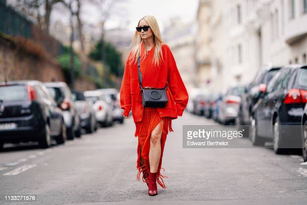 Charlotte Groeneveld wears sunglasses, a red jacket, a red fringed dress, Balenciaga shoes, a black leather bag, outside Elie Saab, during Paris...