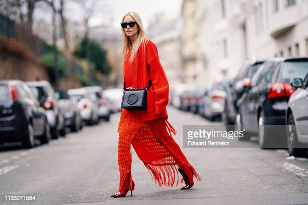 Charlotte Groeneveld wears sunglasses a red jacket a red fringed dress Balenciaga shoes a black leather bag outside Elie Saab during Paris Fashion...