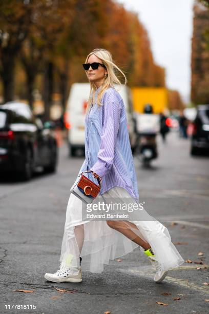 Charlotte Groeneveld wears sunglasses, a white and blue striped oversized shirt, a ruffled flowing white lace skirt, white sneakers, a red crocodile...