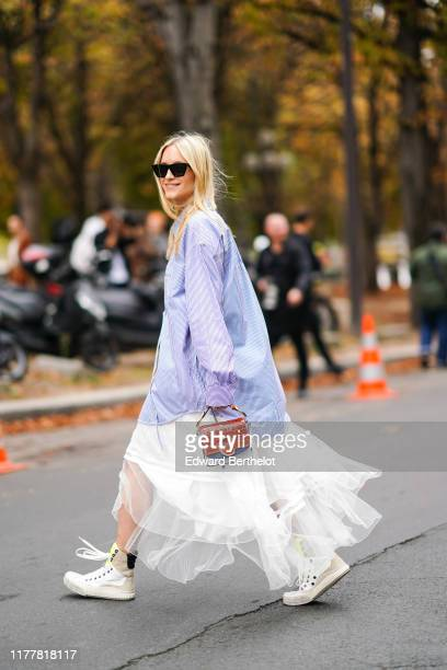 Charlotte Groeneveld wears sunglasses a white and blue striped oversized shirt a ruffled flowing white lace skirt white sneakers a red crocodile...