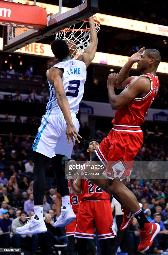 Charlotte Hornets guard Jeremy Lamb, left, throws down a dunk against Chicago Bulls forward/center Cristiano Felicio, right, during second half action on Monday, March 13, 2017 at the Spectrum Center in Charlotte, N.C. The Bulls defeated the Hornets 115-109.