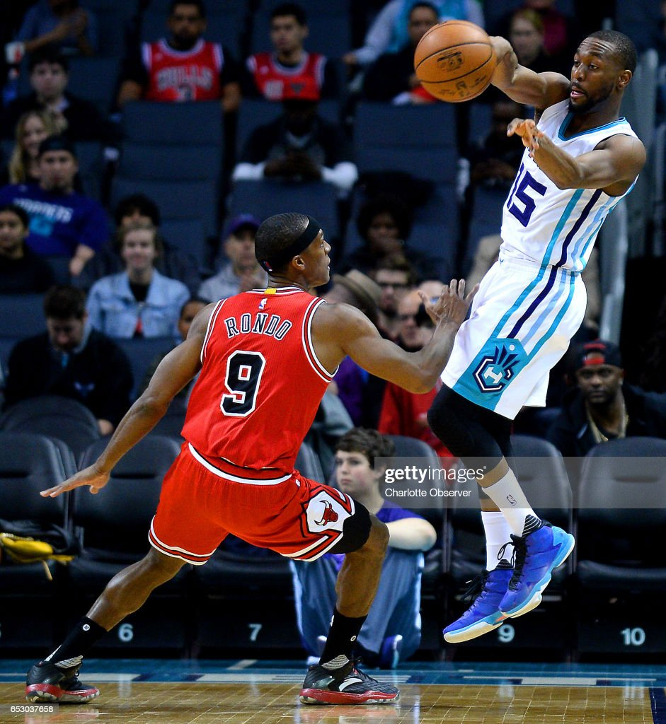 Charlotte Hornets guard Kemba Walker, right, is forced to pass to a teammate as Chicago Bulls guard Rajon Rondo, left, applies defensive pressure during first half action on Monday, March 13, 2017 at the Spectrum Center in Charlotte, N.C.