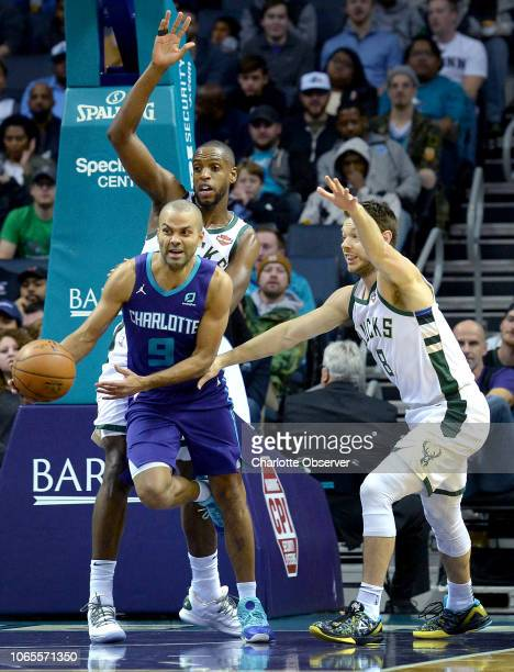 Charlotte Hornets guard Tony Parker, center, escapes a double team by Milwaukee Bucks forward Khris Middleton, back left and guard Matthew...