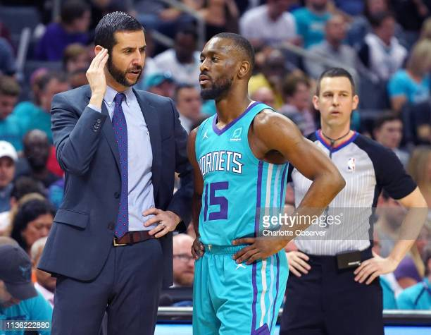 Charlotte Hornets head coach James Borrego left talks with guard Kemba Walker during firsthalf action against the Orlando Magic at Spectrum Center in...