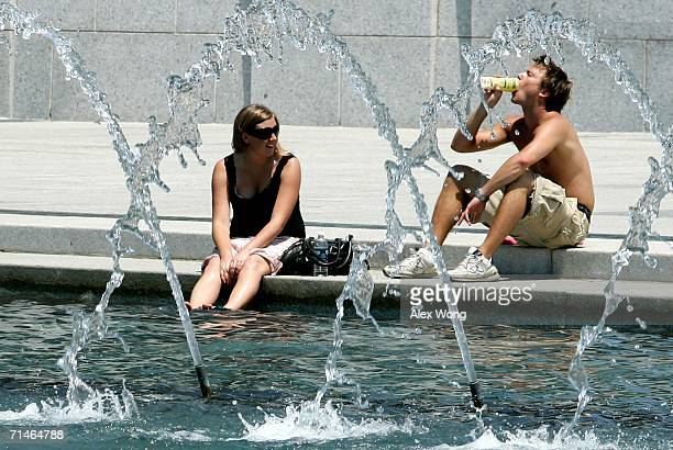 Charlotte Karlsson and her brother Peter of Gotherburg, Sweden, cool themselves off by the fountain as they visit the World War II Memorial July 17,...