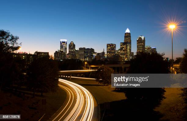 Charlotte North Carolina skyline at night with traffic blurs and twilight