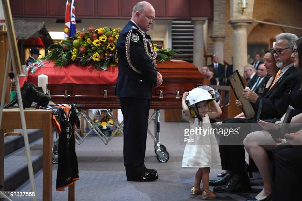 Charlotte O'Dwyer, the young daughter of Rural Fire Service volunteer Andrew O'Dwyer wears her fathers helmet after being presented with her fathers...