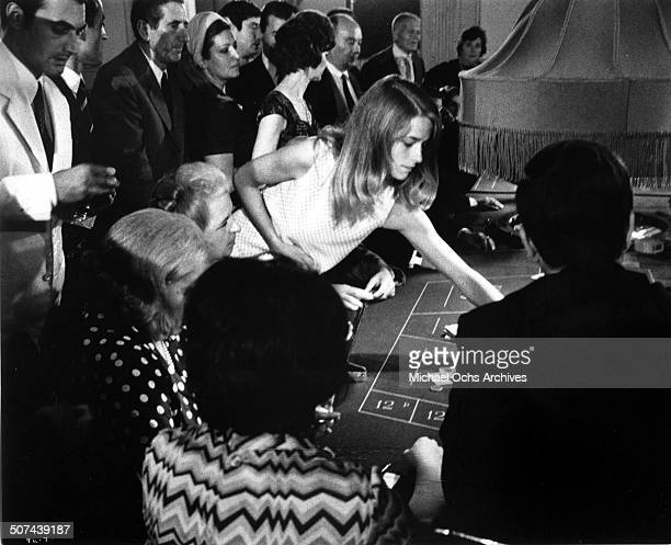 Charlotte Rampling places a bet at a casino in a scene from the movie Three circa 1967