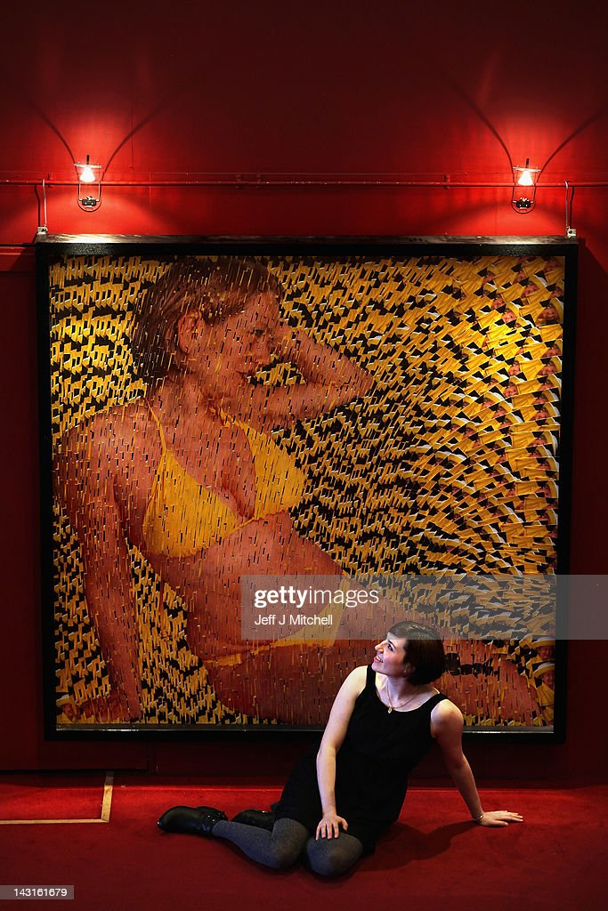 Charlotte Roirdan, from Lyon and Turnbull, poses near portrait of a woman wearing a bikini made entirely out of postcards of the Queen on April 20, 2012 in Edinburgh, Scotland. The portrait Girl in a Yellow Bikini by David Mach, is estimated to raise between £4000 to £6000 at their Scottish Contemporary Sale to be held on April 25.