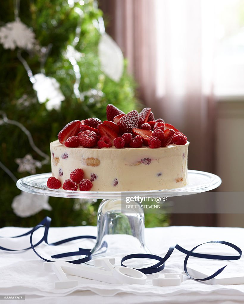 Charlotte russe decorated with strawberries and raspberries on glass cake stand : Stock Photo