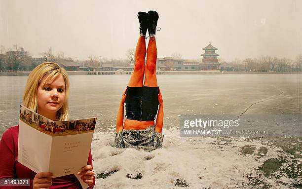 Charlotte Skene from the RMIT Gallery inspect the programme while standing in front of a photograph by Beijing artist Li Wei which shows a person...
