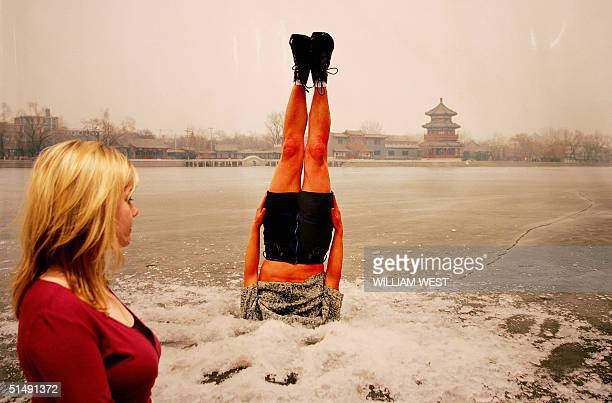 Charlotte Skene from the RMIT Gallery inspects a photograph by Beijing artist Li Wei which shows a person embedded in the ice in Melbourne 18 October...