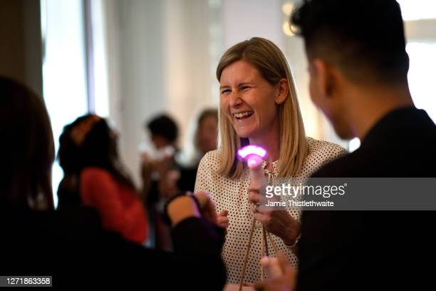 """Charlotte Weatheall laughs at a neon mini fan during the """"Henpire"""" podcast launch event at Langham Hotel on September 10, 2020 in London, England."""