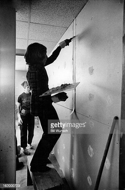 APR 1975 APR 18 1975 Charlotte Winzenburg Puts Tape On Drywall Jane Johnson of Boulder watches her pull drywall finishing knife over tape Hawk holds...
