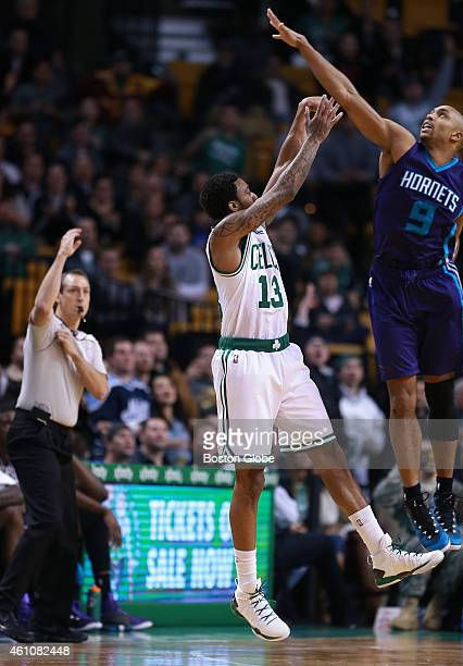 Charlotte's Gerald Henderson right is too late to stop Celtics rookie James Young from taking and hitting a fourth quarter three pointer that cut the...