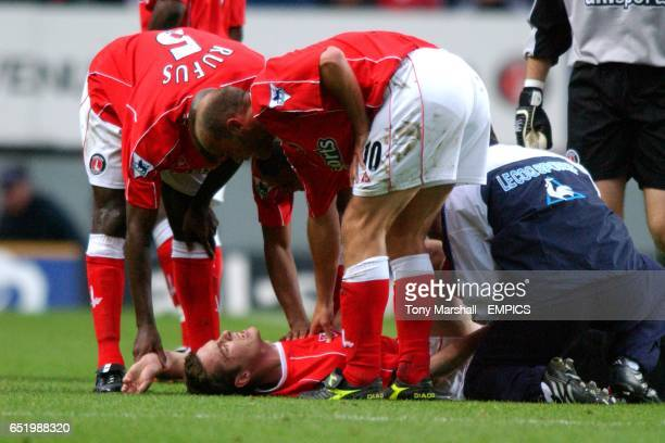 Charlton Athletic's Richard Rufus and Claus Jensen comfort teammate Scott Parker as he is seen to by the physio after a tackle
