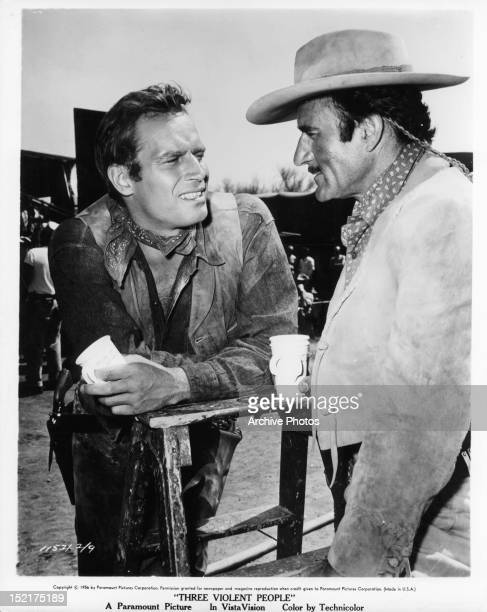 Charlton Heston and Gilbert Roland take a coffee break while on location for the film 'Three Violent People' 1956