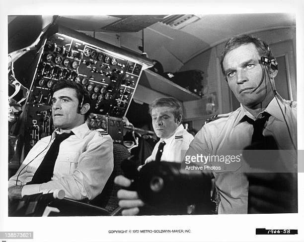 Charlton Heston and other pilots sitting in cockpit in a scene from the film 'Skyjacked' 1972
