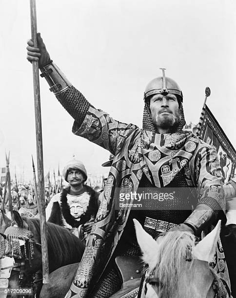 Charlton Heston in a still from the film El Cid. He is riding a horse, at the head of an army, holding a wooden lance.