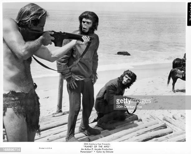 Charlton Heston points a gun next to Roddy McDowall and Kim Hunter in a scene from the film 'Planet Of The Apes' 1968
