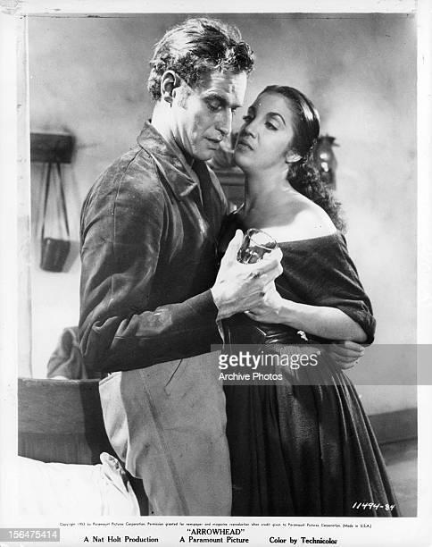 Charlton Heston pulling Katy Jurado close to him in a scene from the film 'Arrowhead', 1953.