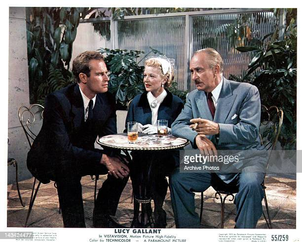 Charlton Heston sitting at small table with Claire Trevor and unidentified man in a scene from the film 'Lucy Gallant' 1955