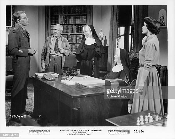 Charlton Heston talking to the school nuns as Julie Adams watches in a scene from the film 'The Private War Of Major Benson' 1955