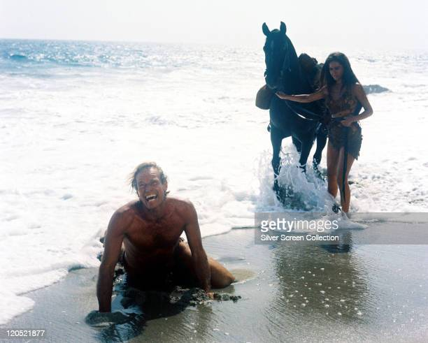 Charlton Heston US actor and Linda Harrison US actress both wearing animal hides alongside Kim Hunter US actress holding a horse as the tide washes...
