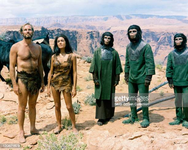 Charlton Heston US actor and Linda Harrison US actress both wearing animal hides alongside Kim Hunter Roddy McDowall and Lou Wagner all dressed in...