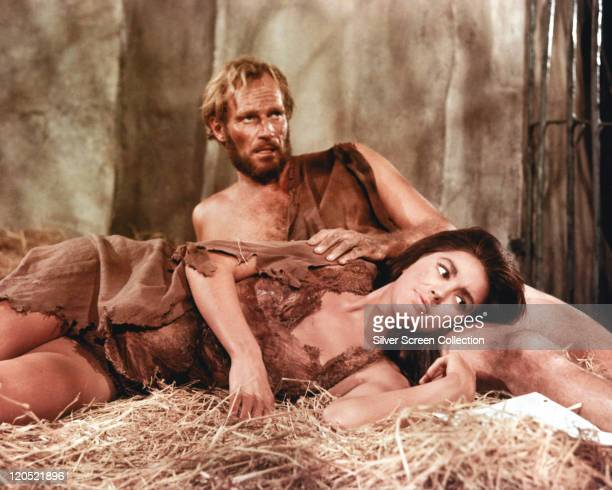 Charlton Heston , US actor, and Linda Harrison, US actress, both wearing animal hides, laying on straw in a publicity still issued for the film,...