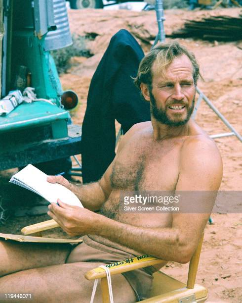 Charlton Heston US actor holding a script as he sits on the set of the film 'Planet of the Apes' 1968 The science fiction film directed by Franklin J...