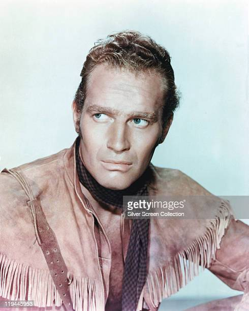 Charlton Heston , US actor, wearing a fringed leather shirt and a check neckerchief, in a publicity portrait issued for the film, 'Pony Express',...