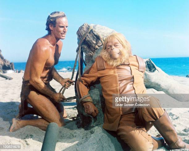 Charlton Heston , US actor, wearing a loin cloth as he ties Maurice Evans , British actor, in costume and wearing an ape mask in a publicity still...