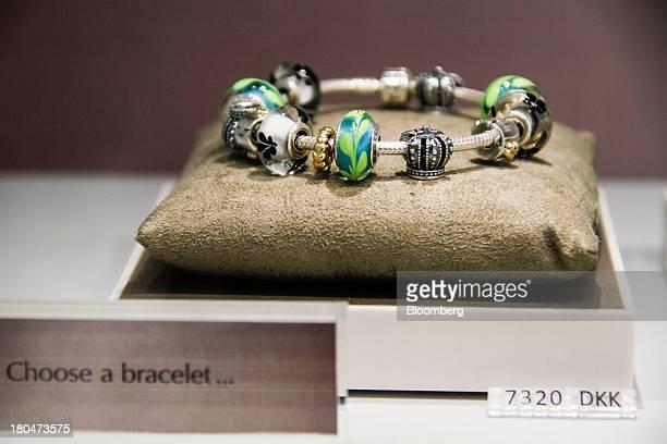 A charm bracelet sits beside a krona price sign inside a Pandora A/S jewelry store in Copenhagen Denmark on Friday Sept 13 2013 The Danish jeweler...