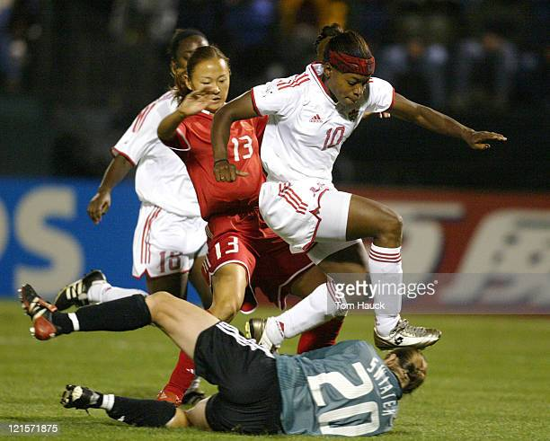 Charmaine Hooper of Canada jumps over teammate Taryn Swiatek as Swiatek makes a save during game action at PGE Park in Portland Oregon October 2 2003...