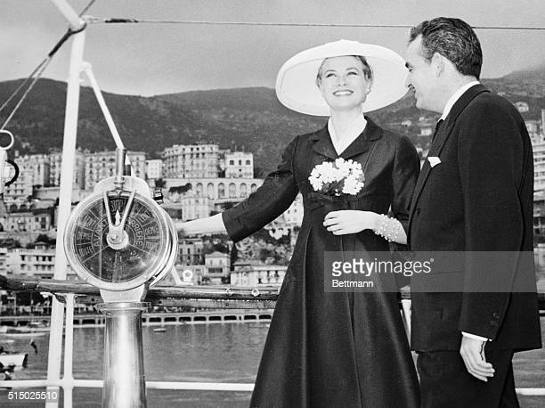 A charming and smiling Grace Kelly stands looking towards the principality of Monaco with her hand on the engine room telegraph of Price Rainer's...