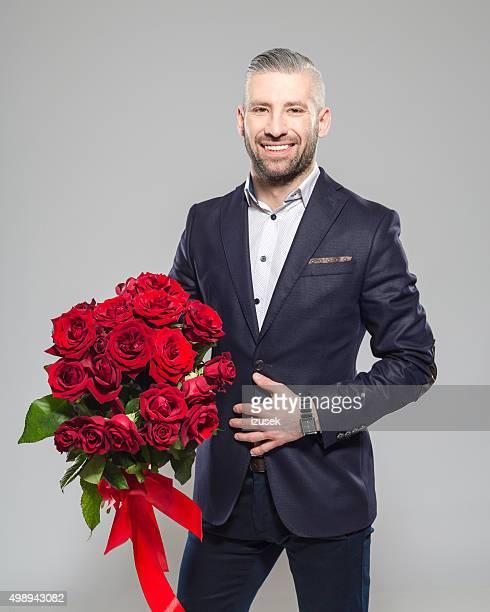 Charmante bärtiger Graues Haar Geschäftsmann holding Haufen Rosen