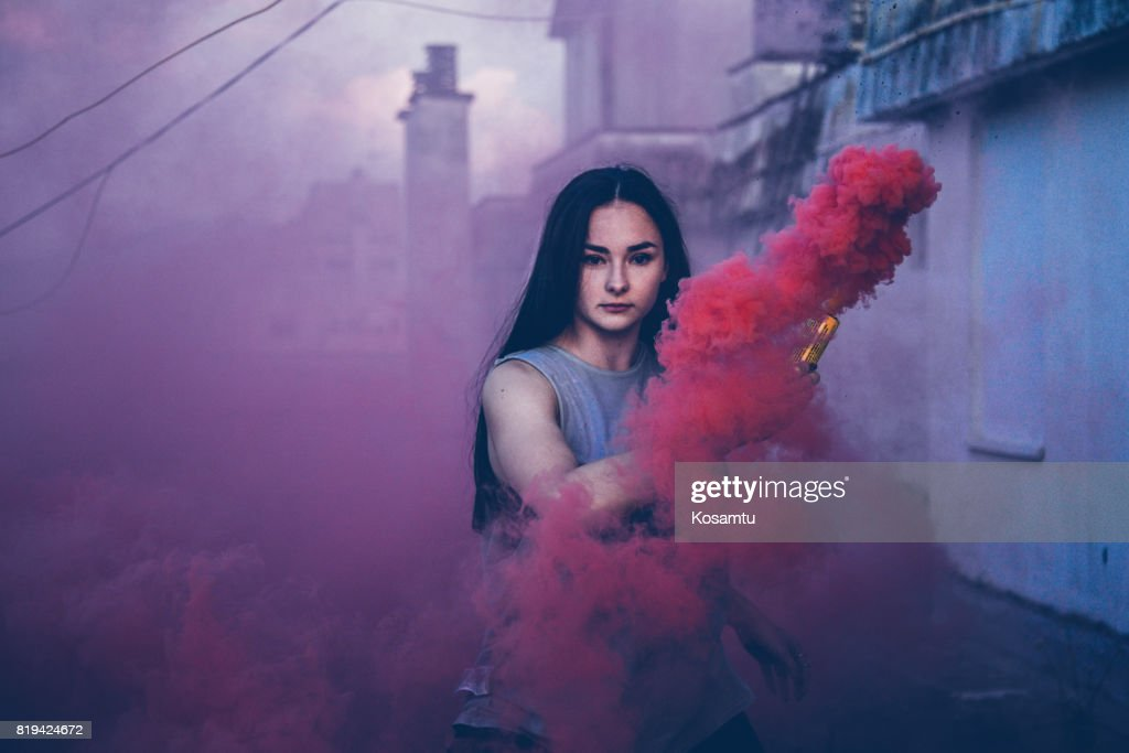 Charming Black-haired Girl Behind Pink Smoke : Stock Photo