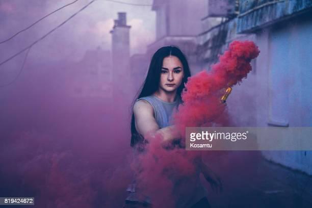 ピンクの煙の背後にある魅力的な黒髪の少女
