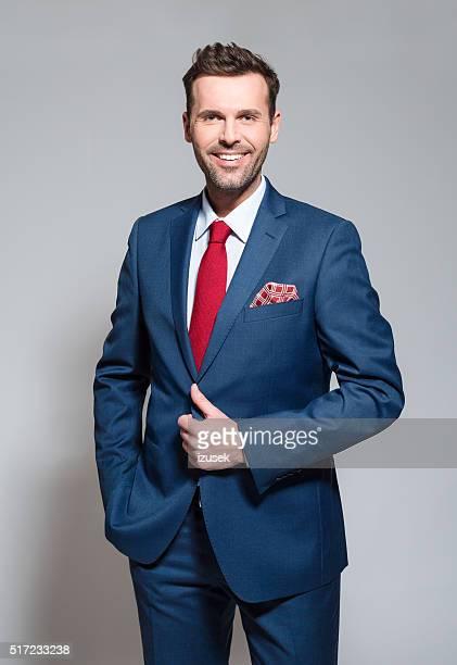 Charming businessman wearing suit, studio portrait