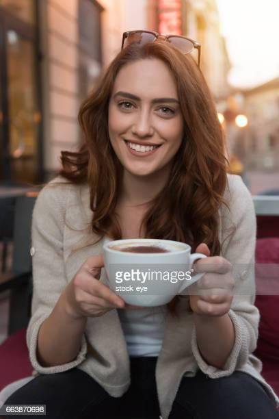 魅力的な女の子のカプチーノを飲み