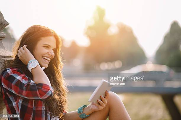 charming girl using tablet - lang haar stockfoto's en -beelden